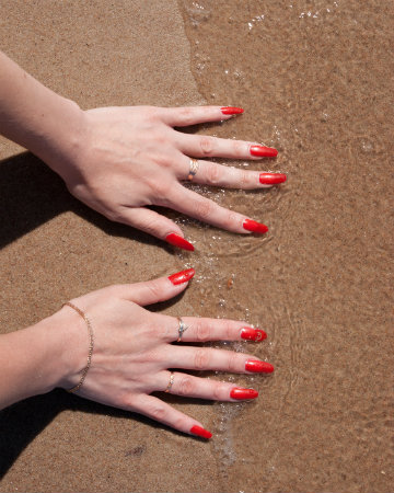 Red manicure at the beach