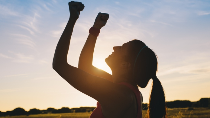 Woman raising arms for celebrating fitness