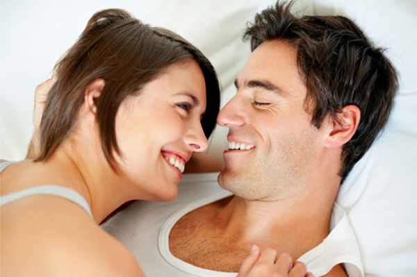 Romantic couple laughing in bed
