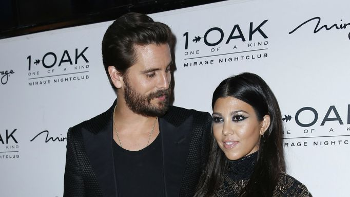 Kourtney Kardashian & Scott Disick posing on red carpet.