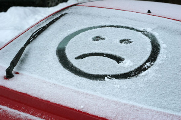 Sad face on car window in snow