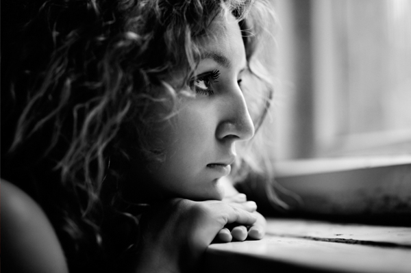 Sad Woman Looking Out Dark Window
