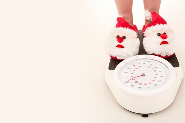 Woman wearing santa slippers on scale
