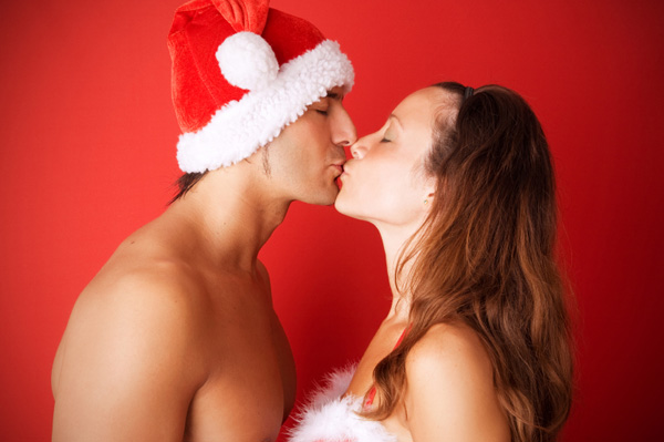 Couple kissing in Christmas outfits