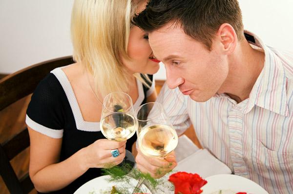 woman whispering in her dates ear