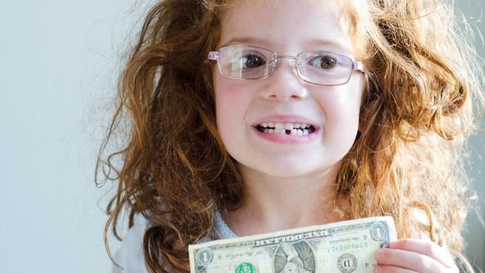 little girl holds a dollar