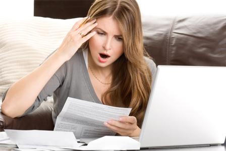 Shocked woman looking at bills