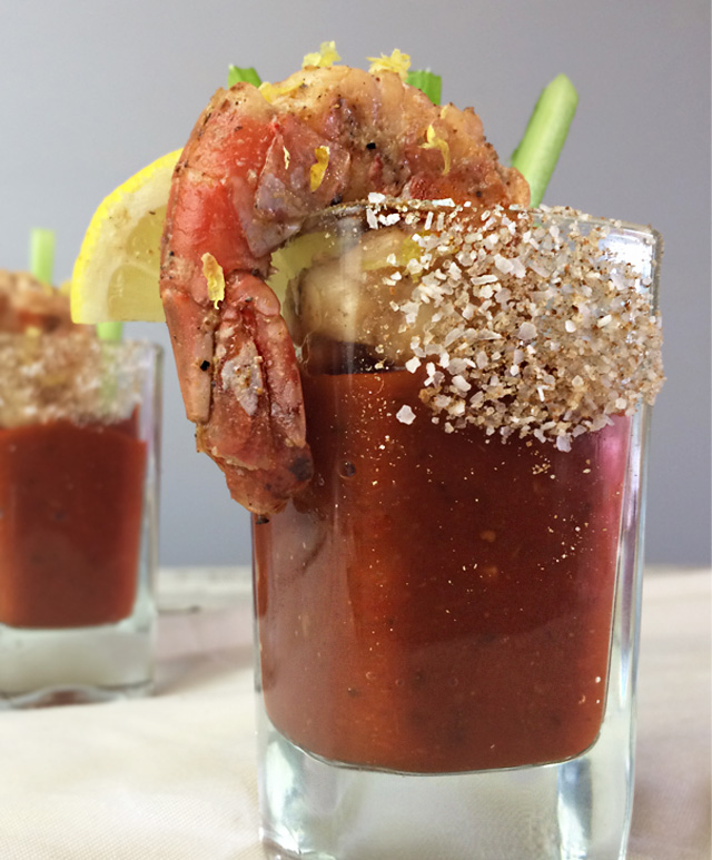 shot glass of bloody mary sauce garnished with a grilled shrimp, lemon and celery matchsticks