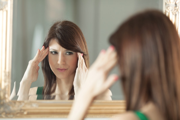 Sick woman looking in mirror