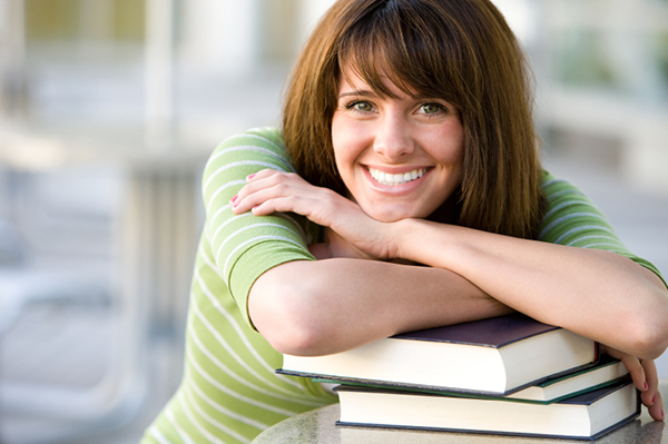 Smiling woman leaning on textbooks | Sheknows.ca