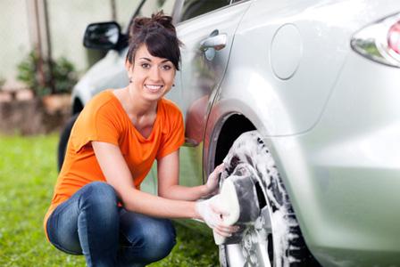 Smiling woman washing car