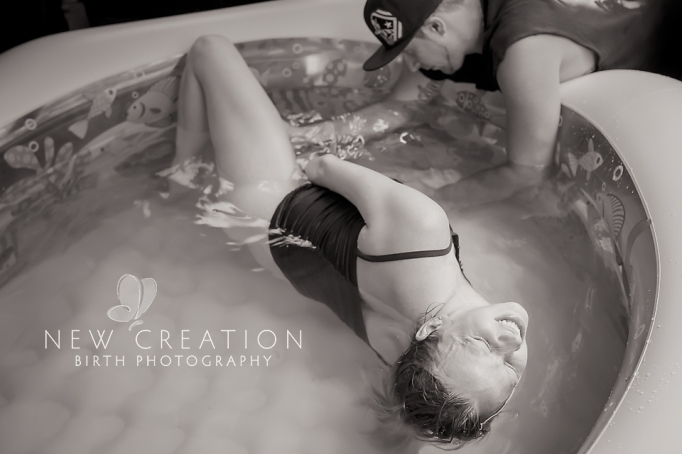 Childbirth photography: A father helps his wife during a water birth