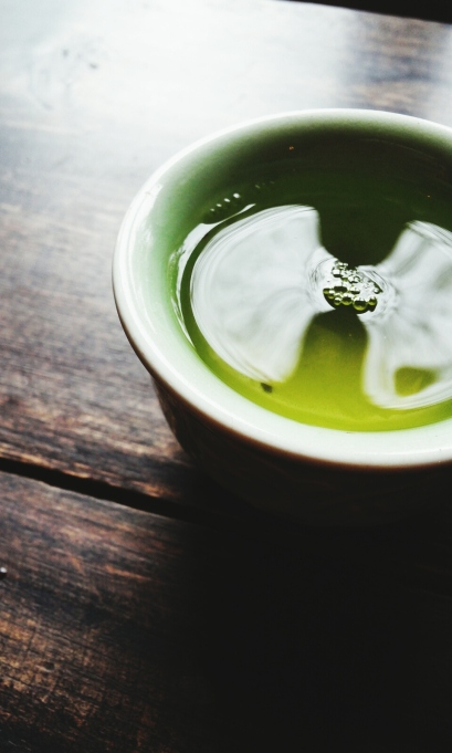 Cup of green tea on wooden table.