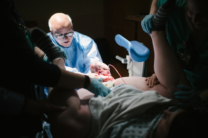 Childbirth photography: A doctor helps delivery an infant