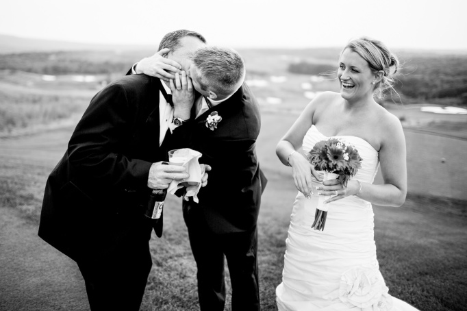 Groom kissing father in law wedding photo