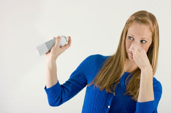 Woman spraying air freshner while plugging nose