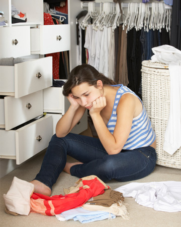 Stressed woman with cluttered closet