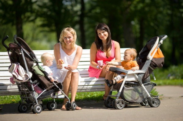 Happy moms at the park with babies in strollers