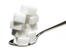 Sugar cubes balanced on a spoon