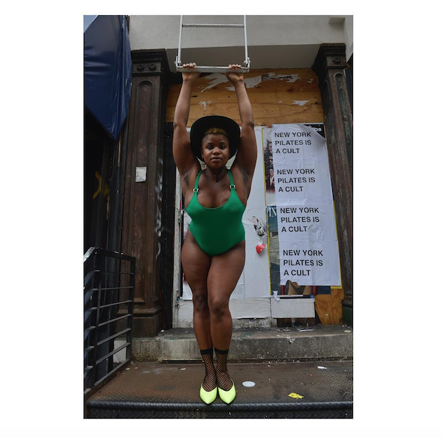 Ericka Hart in a green leotard in front of a pilates sign