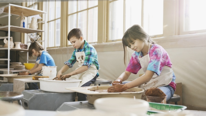 Students using pottery wheels in art
