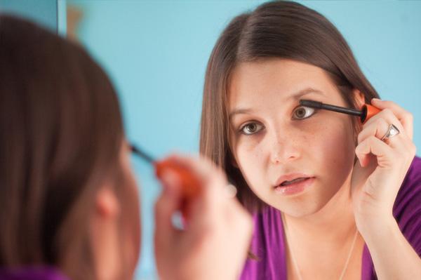 Teen girl applying mascara