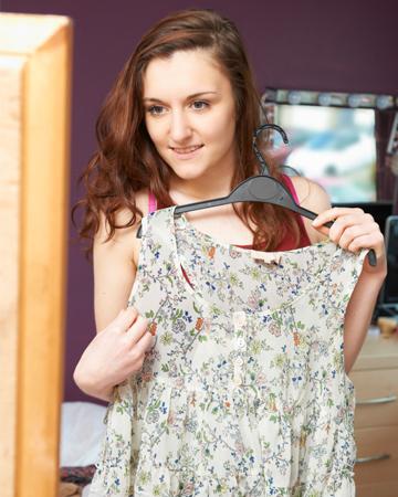 Teen girl trying on shirt