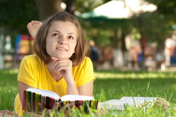 Teen girl reading outdoors