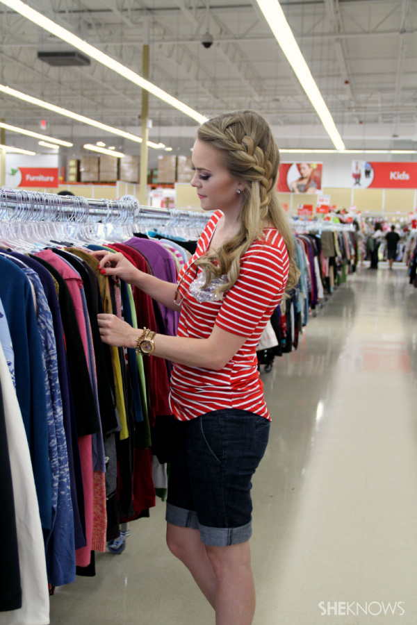 Young woman looking through a thrift store rack