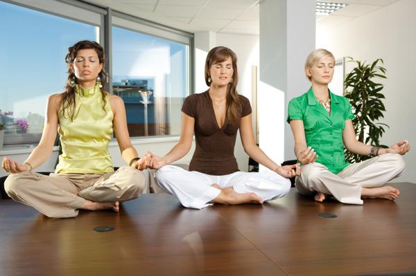 Three business women meditating in office