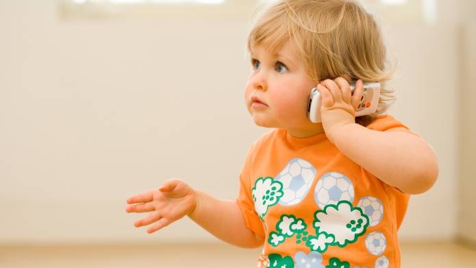 Toddler indoors talking on mobile phone,