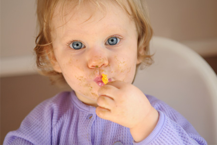 Toddler girl eating solid food