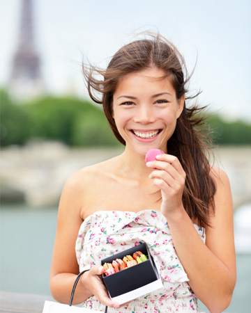 Tourist eating macaroon in France