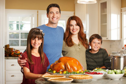 A family standing around a turkey