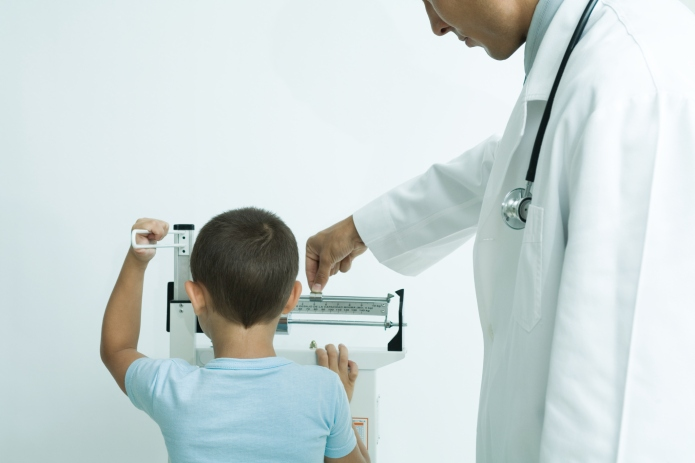 Boy standing on scale at doctor's