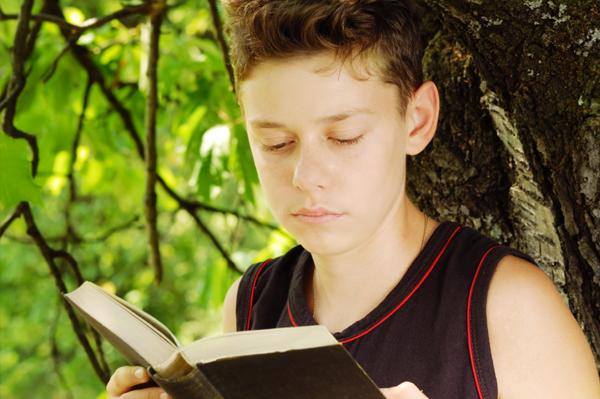 Tween boy reading book