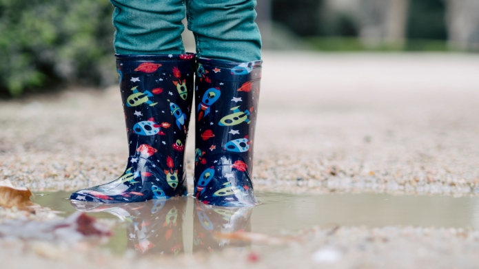 Little boy wearing Wellington boots standing