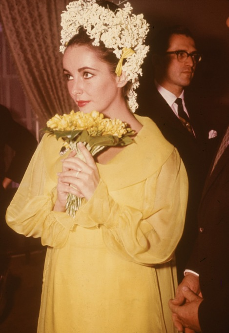Elizabeth Taylor, a yellow dress and floral headdress, holds a bouquet of flowers at her wedding to actor Richard Burton