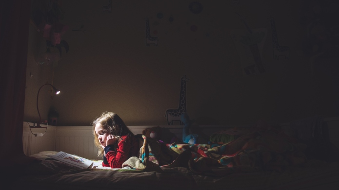 Girl reading in her bed at