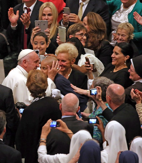 Pope Francis kisses a young girl
