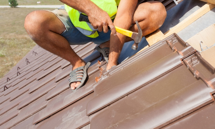 Hands of roofer laying tile on