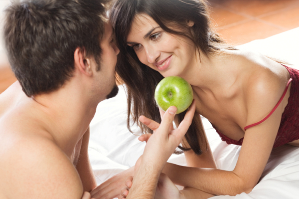 Couple eating apple in bed
