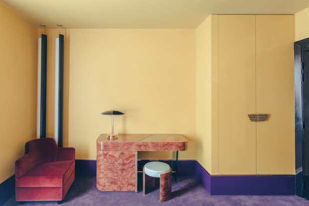 Yellow walls with purple baseboard and carpet