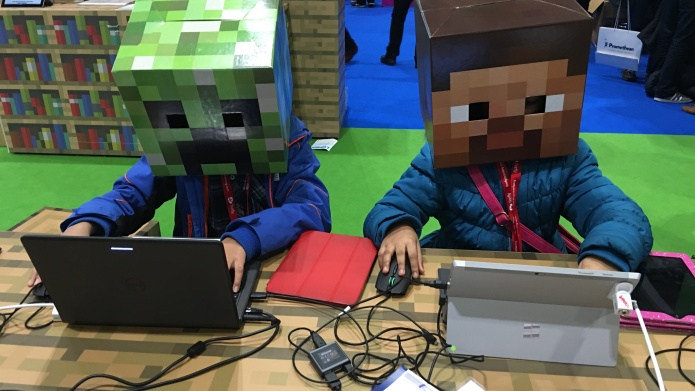 Two students build in Minecraft at