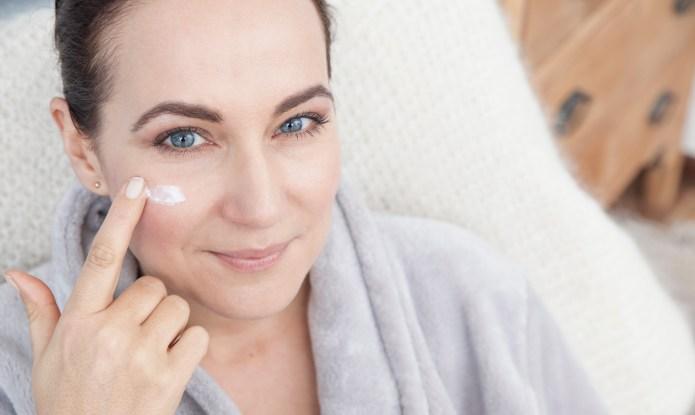 Mature woman applying moisturiser to face