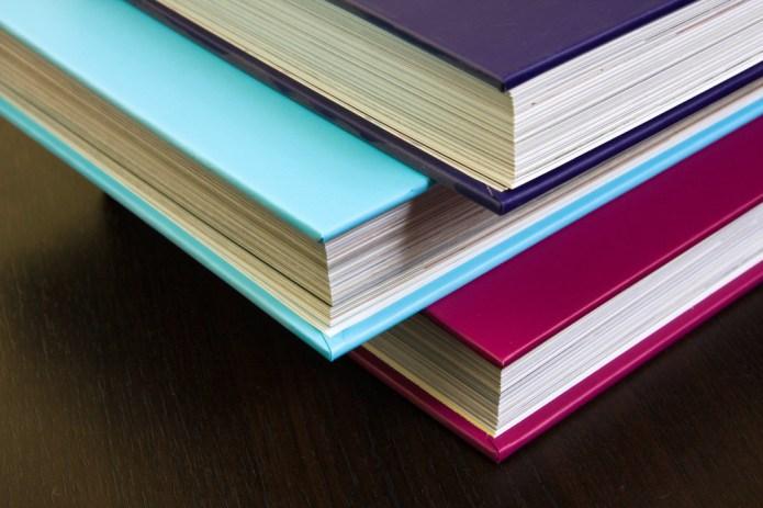 Three thick encyclopedias having brightly colored