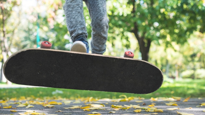 Boy with skateboard in park in