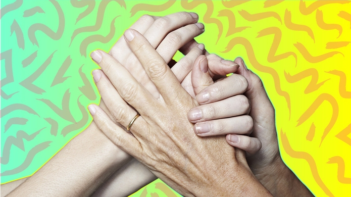 Younger and older woman holding hands