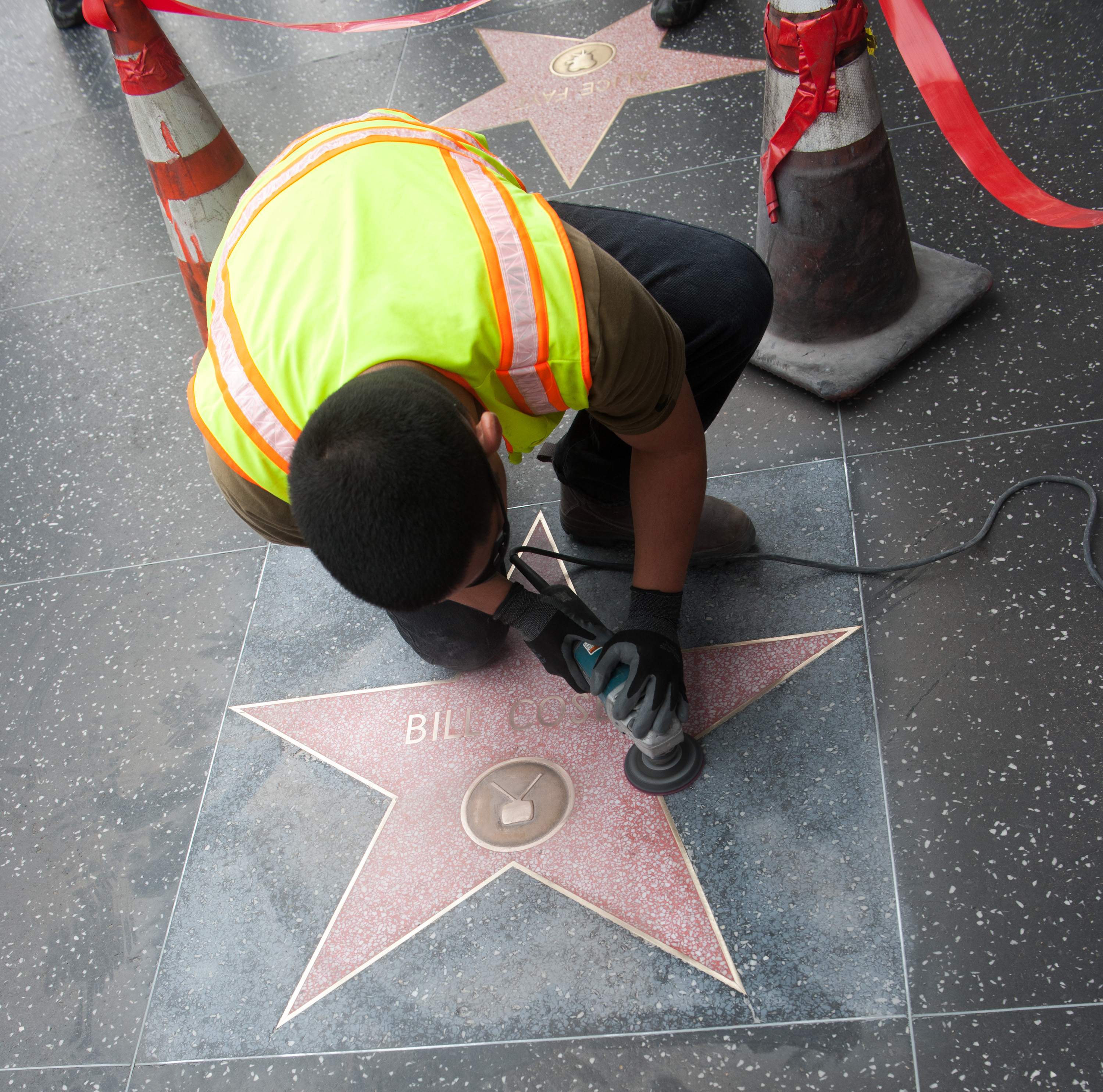 Worker working on Bill Cosyb's hollywood walk of fame star