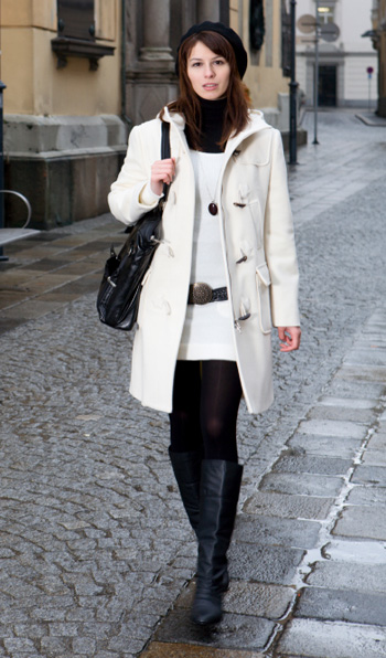 Woman wearing boots and a white coat